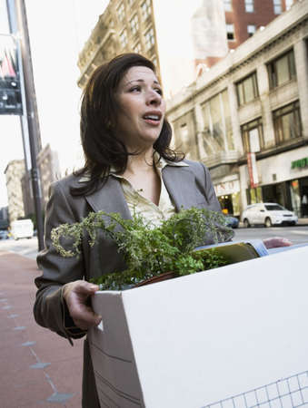 Hispanic businesswoman carrying box of office possessions