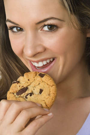 Woman eating chocolate chip cookie