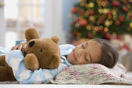 Hispanic girl sleeping in front of Christmas tree LANG_EVOIMAGES