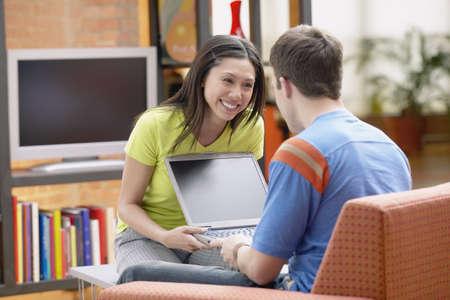 Multi-ethnic couple holding laptop LANG_EVOIMAGES