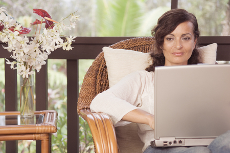 Mature woman typing on laptop LANG_EVOIMAGES