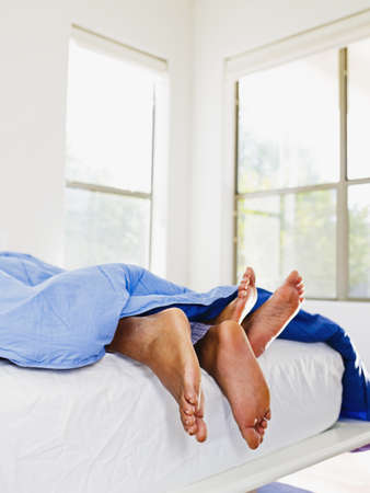 African couple's feet in bed LANG_EVOIMAGES