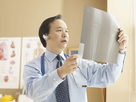 Asian male doctor looking at x-ray LANG_EVOIMAGES