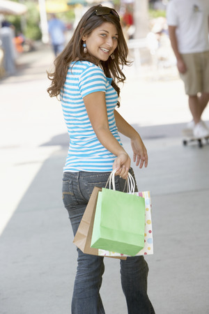 Hispanic woman carrying shopping bags LANG_EVOIMAGES
