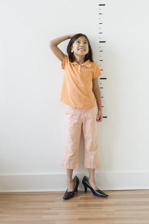 Asijská dívka nosí boty matky před značkami výšky