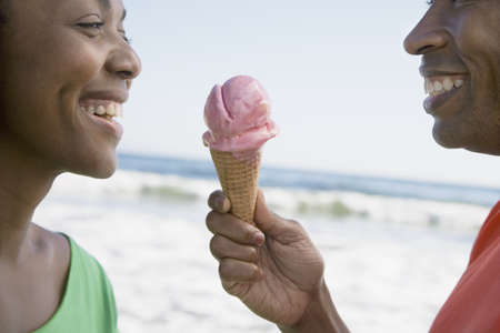 African couple sharing ice cream cone
