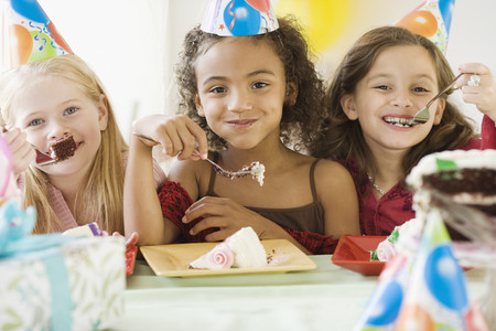 Multi-ethnic girls eating birthday cake LANG_EVOIMAGES