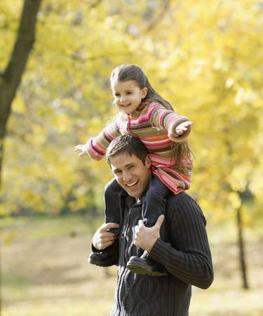 Hispanic father holding daughter on shoulders