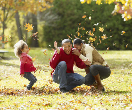 African family playing in autumn leaves