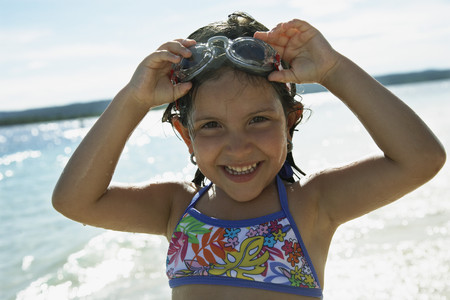 Hispanic girl wearing goggles at beach LANG_EVOIMAGES
