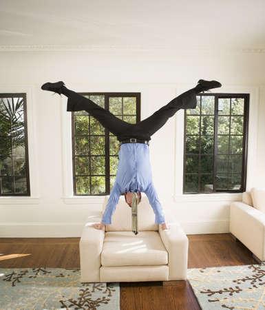 Hispanic businessman doing handstand on chair