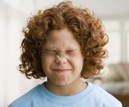 Mixed Race boy with eyes closed tightly LANG_EVOIMAGES