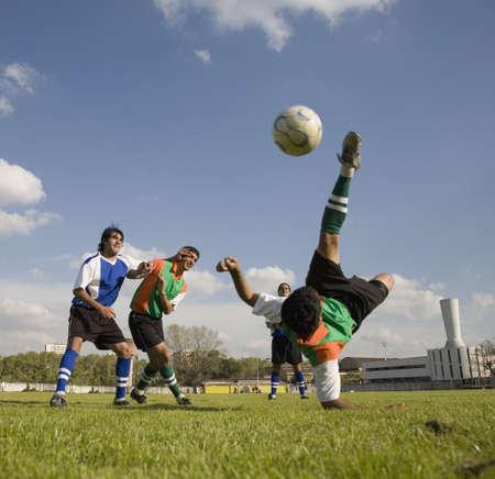 Multi-ethnic men playing soccer LANG_EVOIMAGES