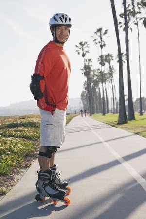 Asian man on rollerblades LANG_EVOIMAGES