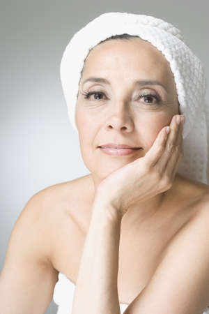 Hispanic woman with hair wrapped in towel LANG_EVOIMAGES