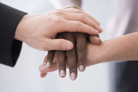 Close up of multi-ethnic hands resting on each other