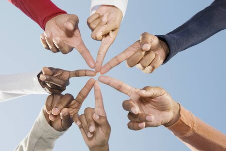 Multi-ethnic friends pointing fingers in circle LANG_EVOIMAGES