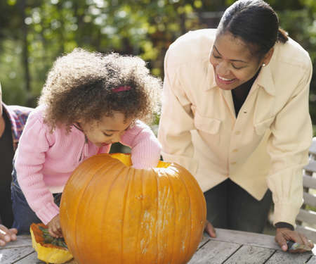 African mother and daughter cleaning out pumpkin
