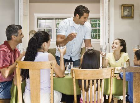 Hispanic family toasting at dinner table
