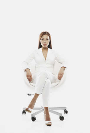 Asian businesswoman sitting in chair LANG_EVOIMAGES