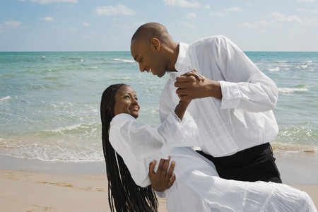 African couple dancing at beach