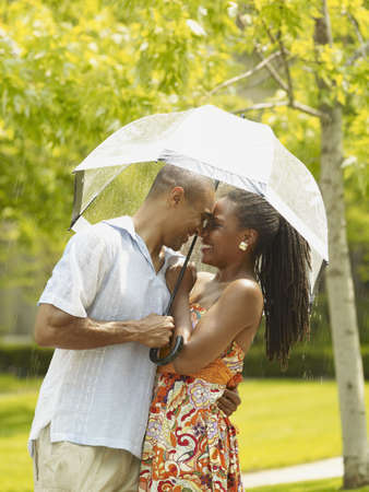 African couple hugging under umbrella