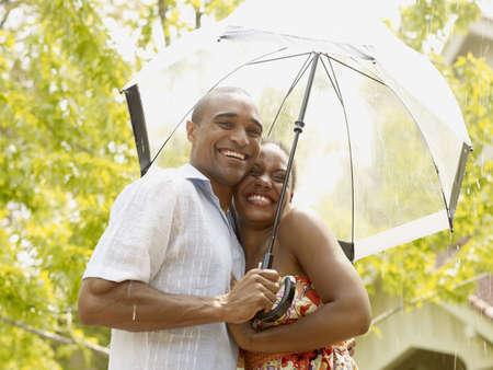 African couple hugging under umbrella