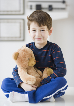 Hispanic boy with teddy bear in doctor's office