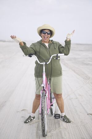 Senior woman with bicycle on beach LANG_EVOIMAGES