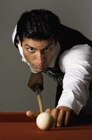 Mixed Race man playing billiards LANG_EVOIMAGES