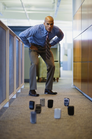 Mixed race man staring at cell phones on office floor LANG_EVOIMAGES