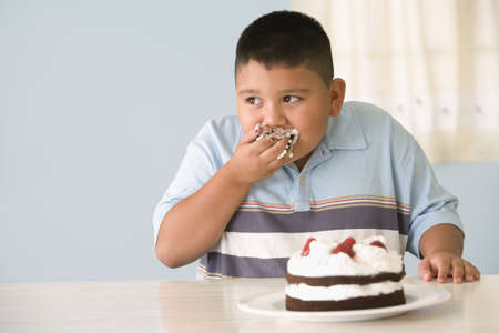 Hispanic boy eating cake with hand LANG_EVOIMAGES