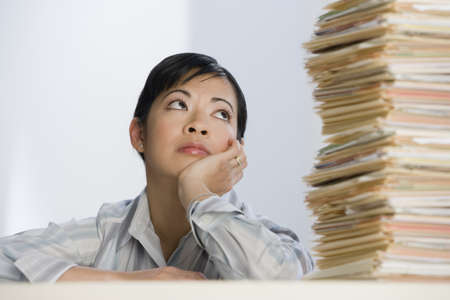 Asian businesswoman looking at stack of paperwork