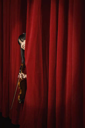 Asian girl holding violin and peeking through curtain