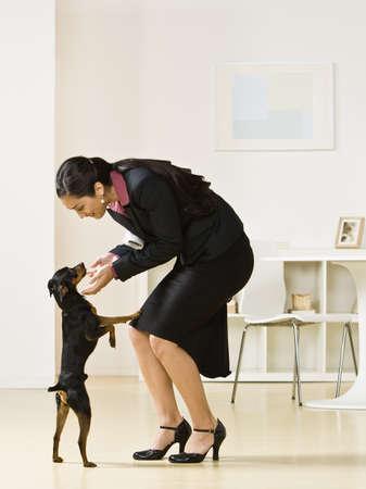Hispanic businesswoman petting dog