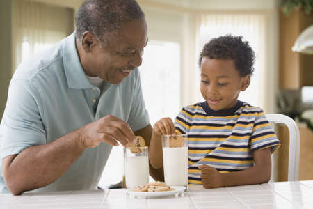 African grandfather and grandson dipping cookies in milk LANG_EVOIMAGES