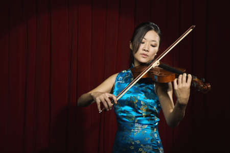 Asian woman playing violin on stage