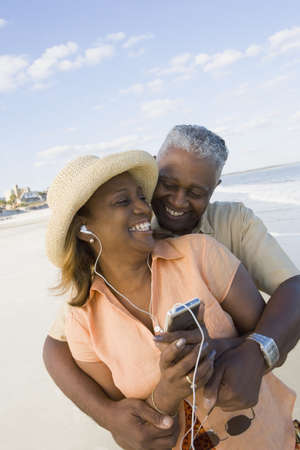 African couple with mp3 player at beach