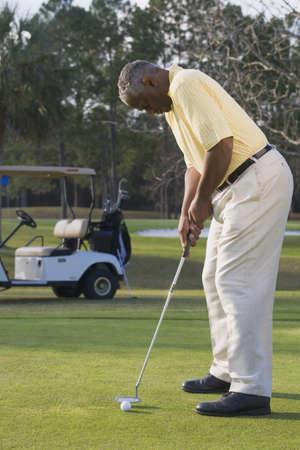 African man playing golf LANG_EVOIMAGES
