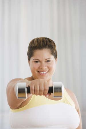 Overweight Hispanic woman lifting dumbbell