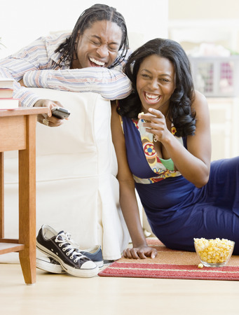 African couple watching television in living room