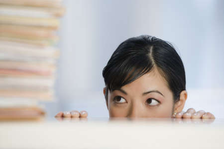 Asian woman peeking over desk at paperwork