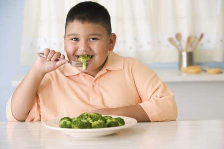 Hispanic boy eating broccoli LANG_EVOIMAGES