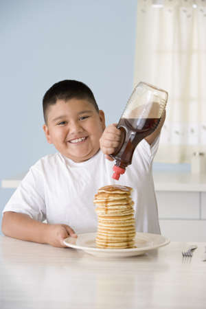 Hispanic boy pouring syrup on pancakes