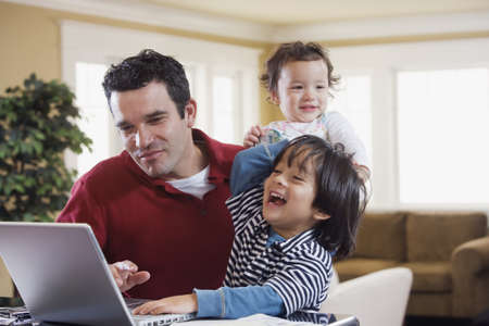 Mixed Race father and children looking at laptop