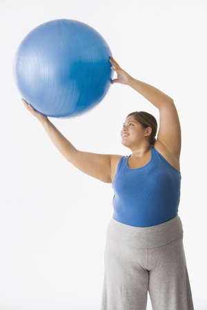 Overweight Hispanic woman exercising with ball
