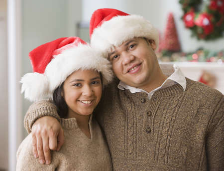 Hispanic father and daughter wearing Santa Claus hats
