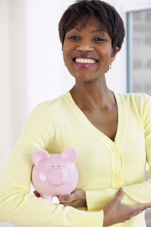 African woman holding piggy bank LANG_EVOIMAGES
