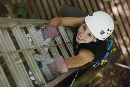 Hispanic woman in hard hat climbing ladder