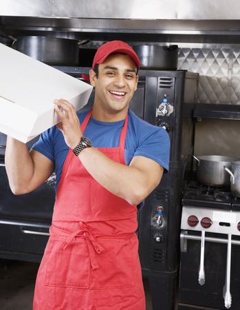 Hispanic male pizza maker holding box LANG_EVOIMAGES